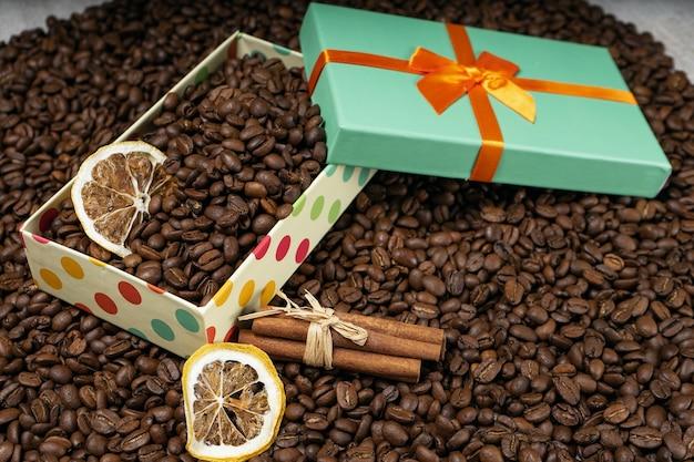 Kawa ziarnista sypana, pudełko upominkowe z suszonymi ziarnami kawy cytrynowej i laskami cynamonu.