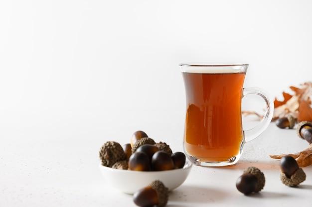 Kawa żołędziowa z liśćmi dębu na białym stole. ścieśniać. miejsce na tekst.