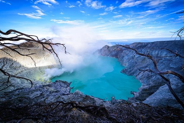 Kawah ijen wulkan z nieżywymi drzewami na niebieskiego nieba tle w jawa, indonezja.