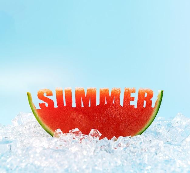 Kawałek arbuza na lodzie, w którym wyryte jest słowo lato.
