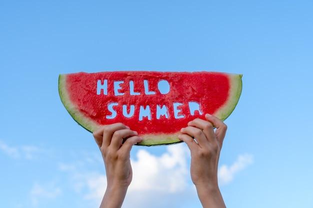Kawałek arbuza na tle błękitnego nieba. ręce dzieci trzymają kawałek arbuza z tekstem hello summer. koncepcja czasu letniego.
