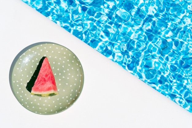 Kawałek arbuza na zielonym talerzu przy koncepcji basenu letnich wakacji i jedzenia