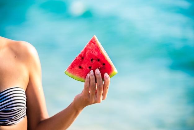 Kawałek arbuza w ręce kobiety nad morzem