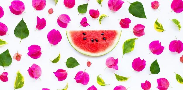 Kawałek arbuza z pięknym czerwonym kwiatem bugenwilli i liśćmi na białym tle. koncepcja tło lato.