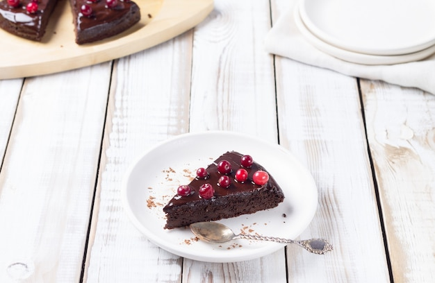 Kawałek bezglutenowego ciasta w czekoladzie, ozdobiony żurawiną, na białym talerzu, na jasnym drewnianym tle. zdrowe desery.