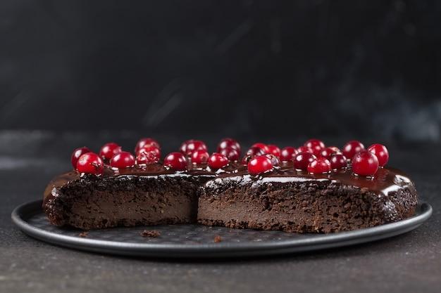 Kawałek bezglutenowego ciasta w czekoladzie, ozdobiony żurawiną, na blaszce, na czarnym tle. skopiuj miejsce. zdrowe odżywianie.