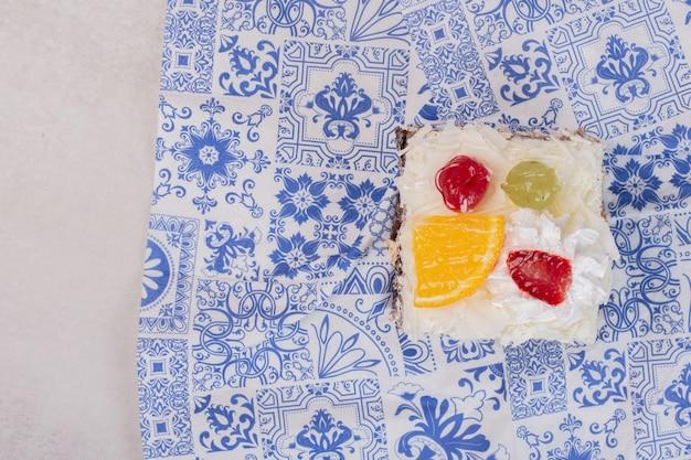 Kawałek białego ciasta z plastrami owoców na obrusie.
