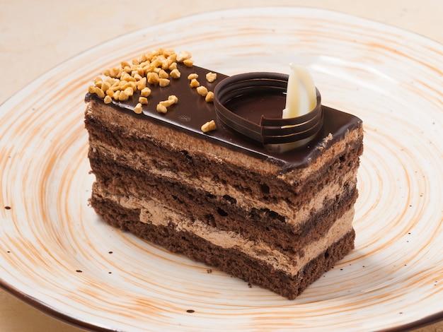 Kawałek biszkoptu czekoladowego ozdobiony orzechami