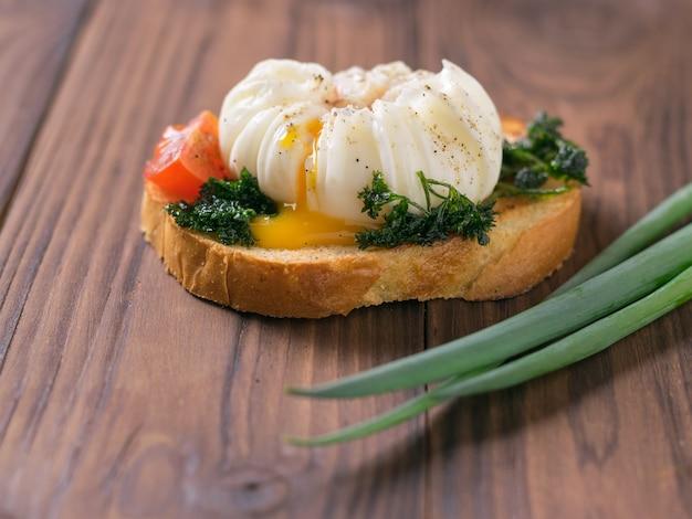 Kawałek chleba tostowego z jajkiem w koszulce na drewnianym stole. wegetariańska przekąska z jajkiem w koszulce.