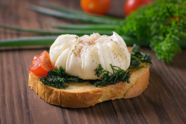 Kawałek chleba z jajkiem w koszulce, zieloną cebulą i pomidorami na drewnianym stole. wegetariańska przekąska z jajkiem w koszulce.
