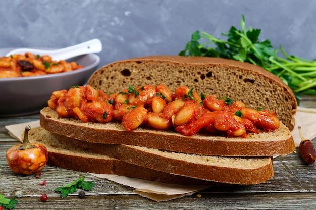 Kawałek chleba żytniego z fasolą. duszona fasola w sosie pomidorowym z ziołami i przyprawami na stole. wielkopostne menu. danie wegańskie