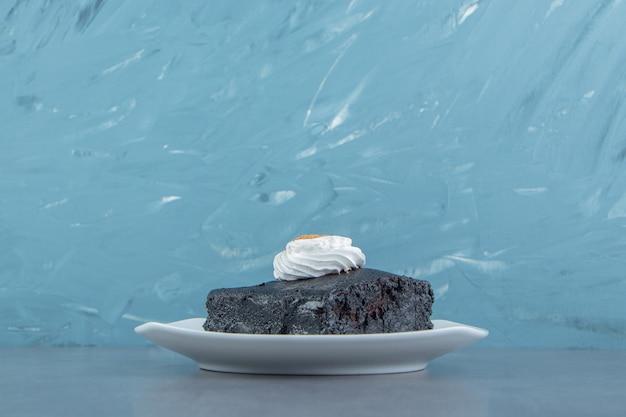 Kawałek ciasta brownie na białej płytce.