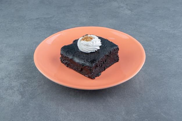 Kawałek ciasta brownie na talerzu pomarańczowym.