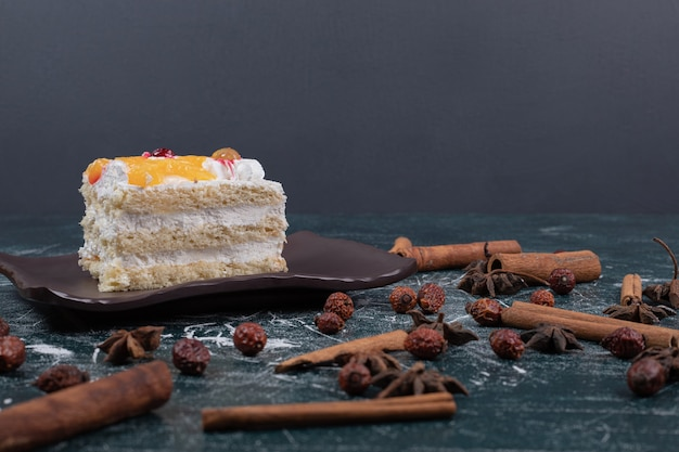 Kawałek ciasta, cynamonów i ziaren kawy na marmurowym stole. wysokiej jakości zdjęcie