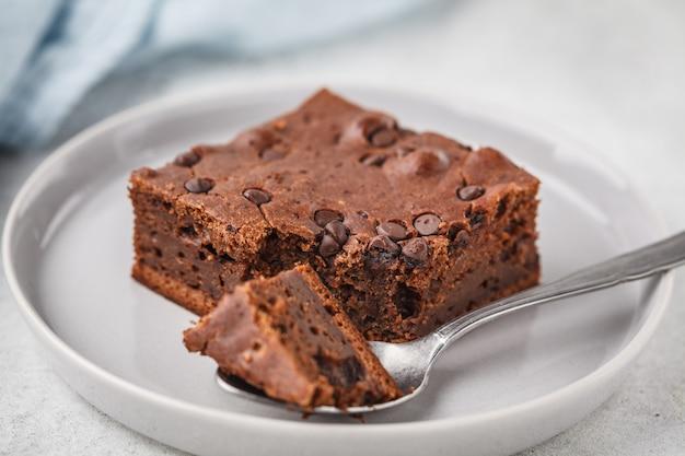 Kawałek ciasta czekoladowe wegańskie z czekoladowymi kroplami i orzechami.