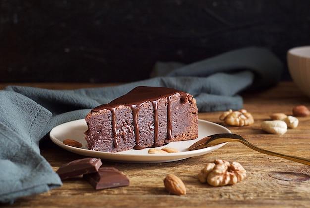 Kawałek ciasta czekoladowego (brownie) na spodku na drewnianym stole. w pobliżu bawełniany ręcznik, łyżka i orzechy. mroczny nastrojowy