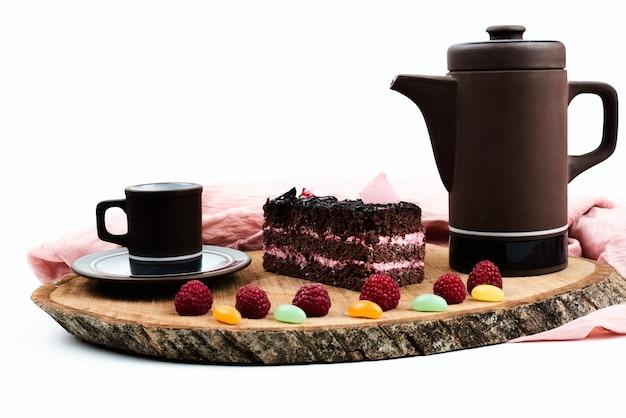 Kawałek ciasta czekoladowego brownie z zestawem do kawy.