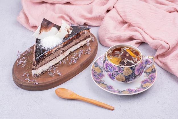 Kawałek ciasta czekoladowego ganache z filiżanką herbaty ziołowej.