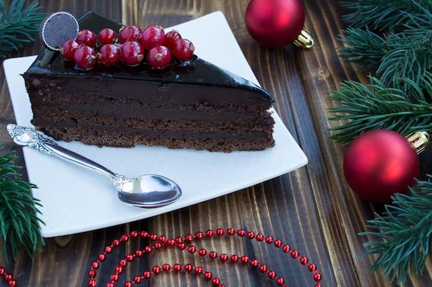 Kawałek ciasta czekoladowego i świąteczna kompozycja na drewnianym stole