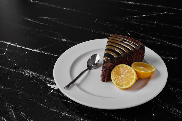 Kawałek ciasta czekoladowego na białym talerzu podawany z cytryną.