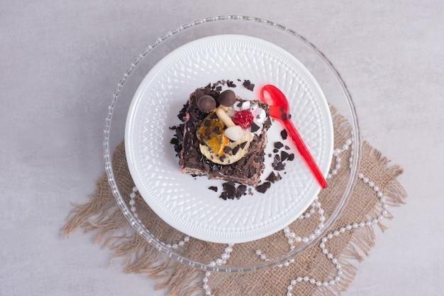 Kawałek ciasta czekoladowego na białym talerzu z perłami.