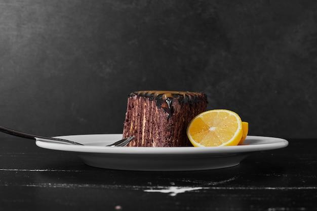 Kawałek ciasta czekoladowego na białym talerzu z plasterkami cytryny.