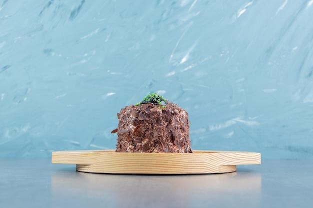 Kawałek ciasta czekoladowego na drewnianym talerzu.