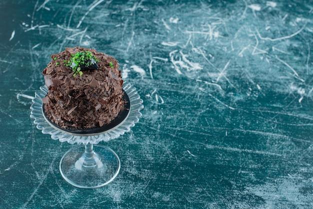Kawałek ciasta czekoladowego na szklanej płytce.