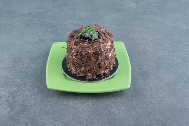 Kawałek ciasta czekoladowego na zielonym talerzu.