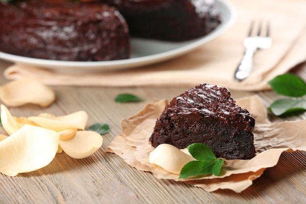 Kawałek ciasta czekoladowego ozdobiony kwiatami na brązowym drewnianym stole