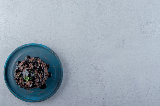 Kawałek ciasta czekoladowego ozdobiony syropem na niebieskim talerzu. zdjęcie wysokiej jakości