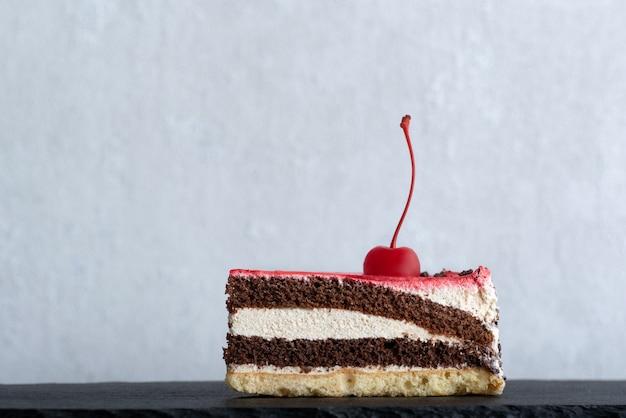 Kawałek ciasta czekoladowego przyozdobionego wiśnią. widok z boku na kawałek ciasta. białe tło.