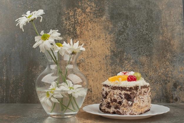 Kawałek ciasta czekoladowego z bukietem rumianku na marmurowej powierzchni.