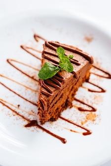 Kawałek ciasta czekoladowego z miętą i polewą czekoladową pod światłami z rozmytym tłem