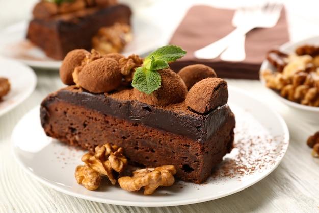 Kawałek ciasta czekoladowego z orzechami i miętą na stole