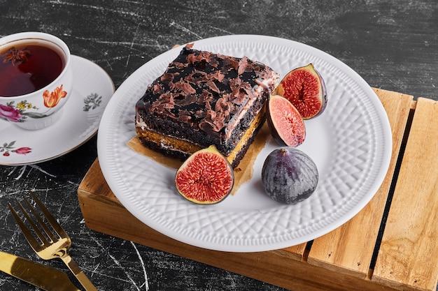 Kawałek ciasta czekoladowego z owocami i filiżankę herbaty w białym talerzu.