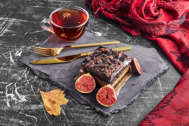 Kawałek ciasta czekoladowego z owocami i filiżankę herbaty.