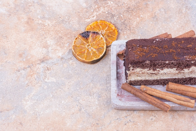 Kawałek ciasta czekoladowego z suchymi plasterkami pomarańczy