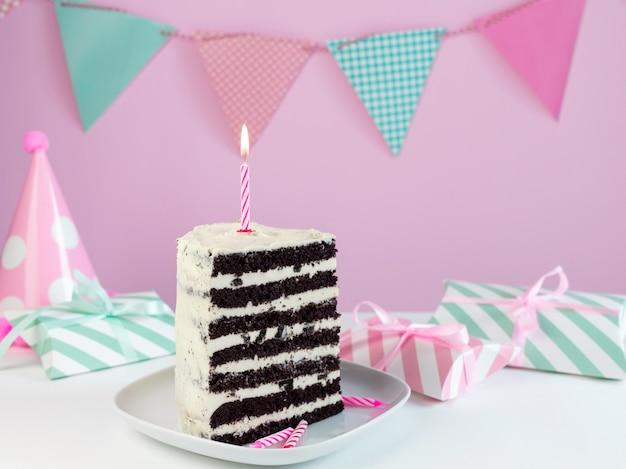 Kawałek ciasta czekoladowego ze śmietaną i świeczką.