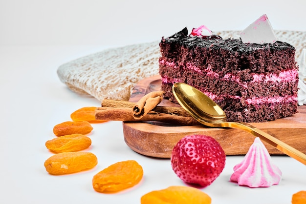 Kawałek ciasta czekoladowo-karmelowego z kremem truskawkowym.
