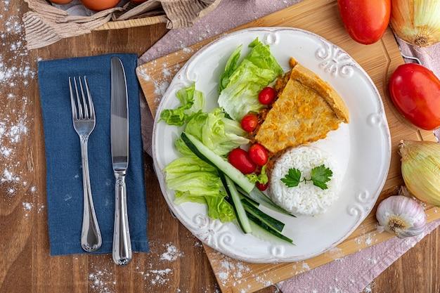 Kawałek ciasta domowego kurczaka na białym talerzu, na drewnianym stole