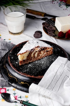 Kawałek ciasta dziennego i nocnego posypany cukrem pudrem podany z mlekiem