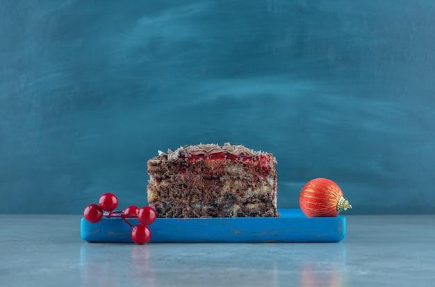 Kawałek ciasta i bombki na talerzu na marmurowej powierzchni