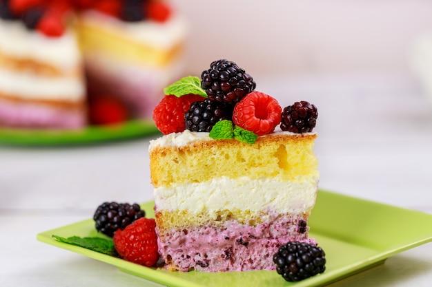 Kawałek ciasta jagodowego ozdobione świeżymi malinami i jeżynami na białym tle.