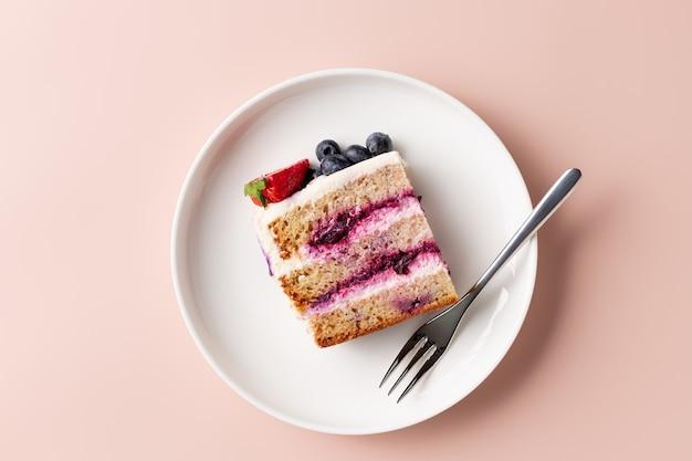 Kawałek ciasta jagodowego ozdobiony świeżymi jagodami na białym talerzu