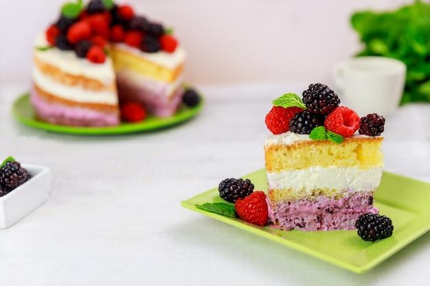 Kawałek ciasta jagodowego ozdobiony świeżymi malinami i jeżynami na białym stole.