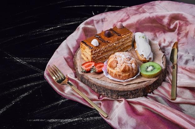Kawałek ciasta karmelowego na drewnianym talerzu.