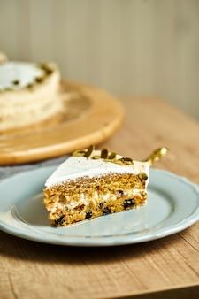 Kawałek ciasta marchewkowego domowej roboty na talerzu. drewniane tło