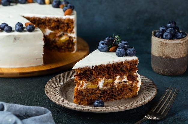 Kawałek ciasta marchewkowego z orzechami włoskimi i jagodami na ciemnym tle drewna. lokalne jedzenie. tradycyjne amerykańskie ciasto. ciasto na święto dziękczynienia. ciasto świąteczne.