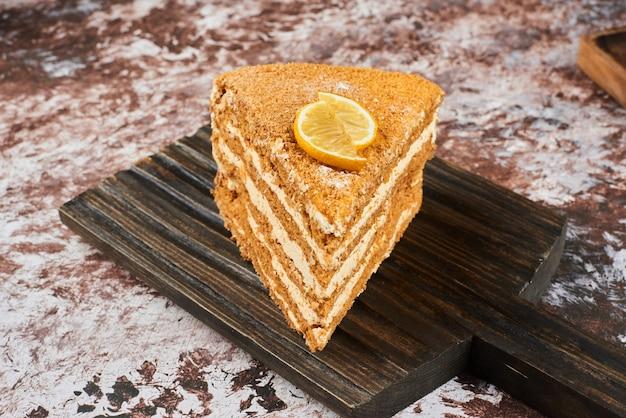 Kawałek ciasta miodowego na drewnianym talerzu.
